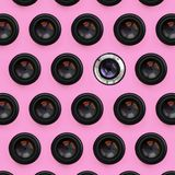 A few camera lenses with a closed aperture lie on texture background of fashion pastel pink color paper in minimal concept. Abstract trendy pattern royalty free stock photography