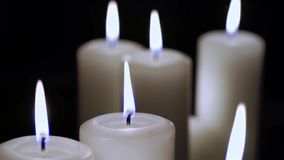 A few candles are burning on a black background. stock footage
