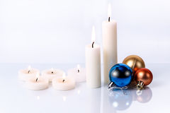 A few candles and Christmas toys of different sizes. On a light background, with reflection Stock Image