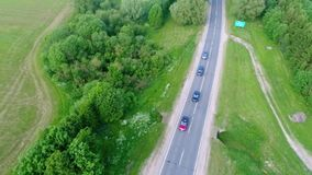 A few cars travel on a suburban road stock footage