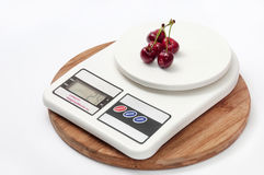FEW CHERRIES WHITE DIGITAL SCALE WOODEN BOARD Stock Photography