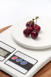 FEW CHERRIES WHITE DIGITAL SCALE WOODEN BOARD Royalty Free Stock Image