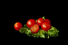 A few cherry tomatoes on a salad leaf. Several cherry tomatoes on fresh lettuce leaves on a black background Royalty Free Stock Photos