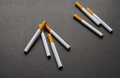 A few cigarets on dark background. A few cigarets of tobacco on dark bakcground Royalty Free Stock Photos
