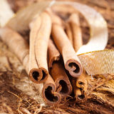 A few cinnamon sticks on wooden background. An a golden bow Stock Photography