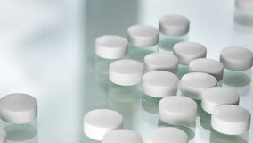 Few circle tablet antibiotic medical supplement falling on white. Shot on RED Raven hospital Cinema Camera