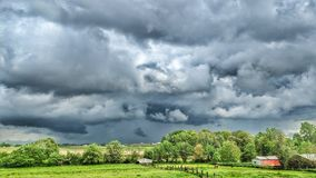 A few clouds in the weather forecast. Turbulent but sunny skies blanket across a farm field stock image