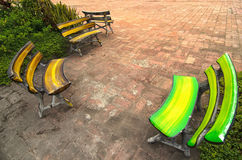 Few colorful benches oposit each other on a brick square - tradi Stock Image