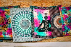 Few colorful Buddhist hanging tapestry hung on a wall for sale. A few colorful Buddhist hanging tapestry hung on a wall for sale stock photos