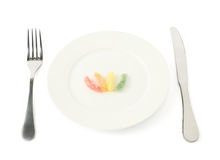 Few colorful candies in a plate isolated Royalty Free Stock Photos