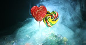 Few colorful candy heart lollipops on different colored candies against dark toned foggy background. Selective focus stock video footage