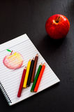 Few colorful pencils on sketchbook with hand draw art red apple sketch on lined paper on dark wooden table surface with read apple Royalty Free Stock Photography