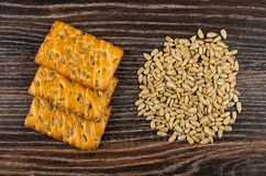 Cookies with sunflower seeds, heap of peeled seeds on dark wooden table. Top view royalty free stock photo