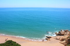 A few couples of swimmers enjoy wonderful weather in Calella de Costa's Rocapins beach. Royalty Free Stock Images