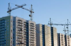 Few cranes crane yellow finish building multi-storey. Residential building. construction work using heavy machinery Stock Photography
