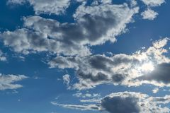 Few Cumulus clouds blotted out the sun. The sun`s rays breaking through a cloud with ragged edges. Atmosphere before the rain. Background, backdrop or royalty free stock photos