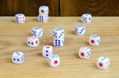 A few dice lies on the surface of natural wood. Items for generating numbers from one to six in the form of points that are paint. Ed on the side of cubes. The Royalty Free Stock Image