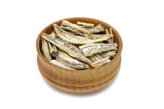 A few dried anchovies in wooden bowl Stock Photo