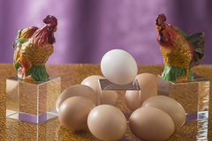 A few eggs on a bright background. Brown and white eggs on a relief glass background Royalty Free Stock Images