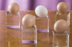 A few eggs on a bright background. Brown and white eggs on a relief glass background Royalty Free Stock Photo