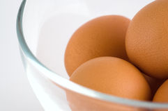 Few eggs in glass bowl. In closeup at isolated white background Royalty Free Stock Photo