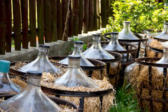 Few Empty Glass Vine Demijohns with Fence Behind. Empty Glass Vine Demijons Covered by Straw Stock Photos