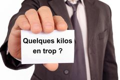 A few extra pounds written in French. Unrecognizable man holding a card on which is written in French a few extra pounds royalty free illustration