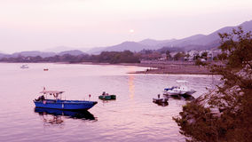 Few fishing boats in water bay at sunset Stock Photos
