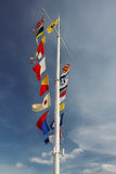 Few flags on white pole at blue cloudy sky Royalty Free Stock Image