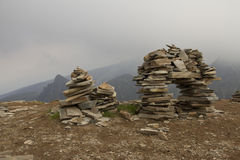 Few flat stones stacked pyramid atop a mountain on. A few flat stones stacked pyramid atop a mountain on the background of clouds Royalty Free Stock Images