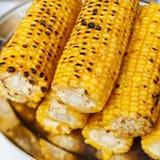 A few fried corn cobs lie on a metal dish.  Stock Photo
