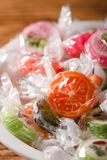 Few fruit candies with fruit motifs in white bowl Stock Photos