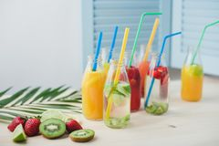 A few glass bottles on table with different fruit coctails. stock photography