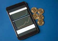 Few gold  bitcoins lie on the table in front of and next to the tablet on which charts of Bitcoins cost growth are visible. Royalty Free Stock Photos