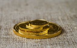 A few gold coins on a background of rough wood texture. Selective focus Stock Photography