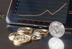 Few gold bitcoins lie on the table in front of and next to the tablet on which charts of Bitcoin& x27;s cost growth are visible. Royalty Free Stock Image