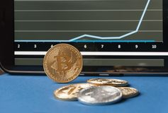Few gold  bitcoins lie on the table in front of and next to the tablet on which charts of Bitcoin& x27;s cost growth are visible. Stock Photography
