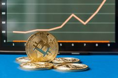 Few gold  bitcoins lie on the table in front of and next to the tablet on which charts of Bitcoin& x27;s cost growth are visible. Royalty Free Stock Images