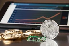 A few gold and silver   coins bitcoin lie on a blue background Concept of crypto currency Stock Photos