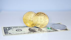 Few gold and silver coins of bitcoin on dollar bills as a symbol. Several gold and silver coins of bitcoin on dollar bills as a symbol of a new currency Royalty Free Stock Photography