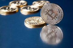 A few gold and silver   coins bitcoin lie on a blue background Concept of crypto currency. Stock Photography