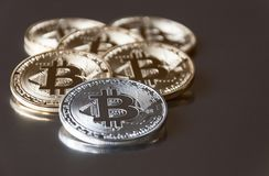 A few gold and silver coins bitcoin lie or stay on edge on a dark background. The concept of crypto currency. Stock Photos
