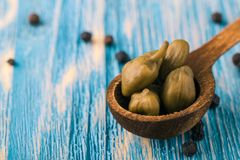 Few green capers on blue wooden table with spice around Stock Image