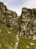 Hikers Climb Steep Path Between Rock Formations royalty free stock photography