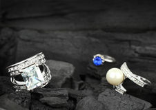 Few jewelry rings with brilliants, gems and pearl on dark coal b Royalty Free Stock Photography