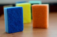 A few kitchen sponges lie on a wooden kitchen countertop. Colorful objects for washing dishes and cleaning in the house are ready Stock Images