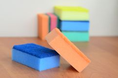A few kitchen sponges lie on a wooden kitchen countertop. Colorful objects for washing dishes and cleaning in the house are ready Royalty Free Stock Image