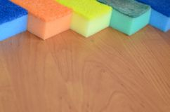 A few kitchen sponges lie on a wooden kitchen countertop. Colorful objects for washing dishes and cleaning in the house are ready Royalty Free Stock Photography