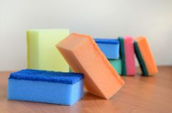 A few kitchen sponges lie on a wooden kitchen countertop. Colorful objects for washing dishes and cleaning in the house are ready stock photography