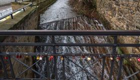 Few love locks on a small bridge above a river in europe royalty free stock image